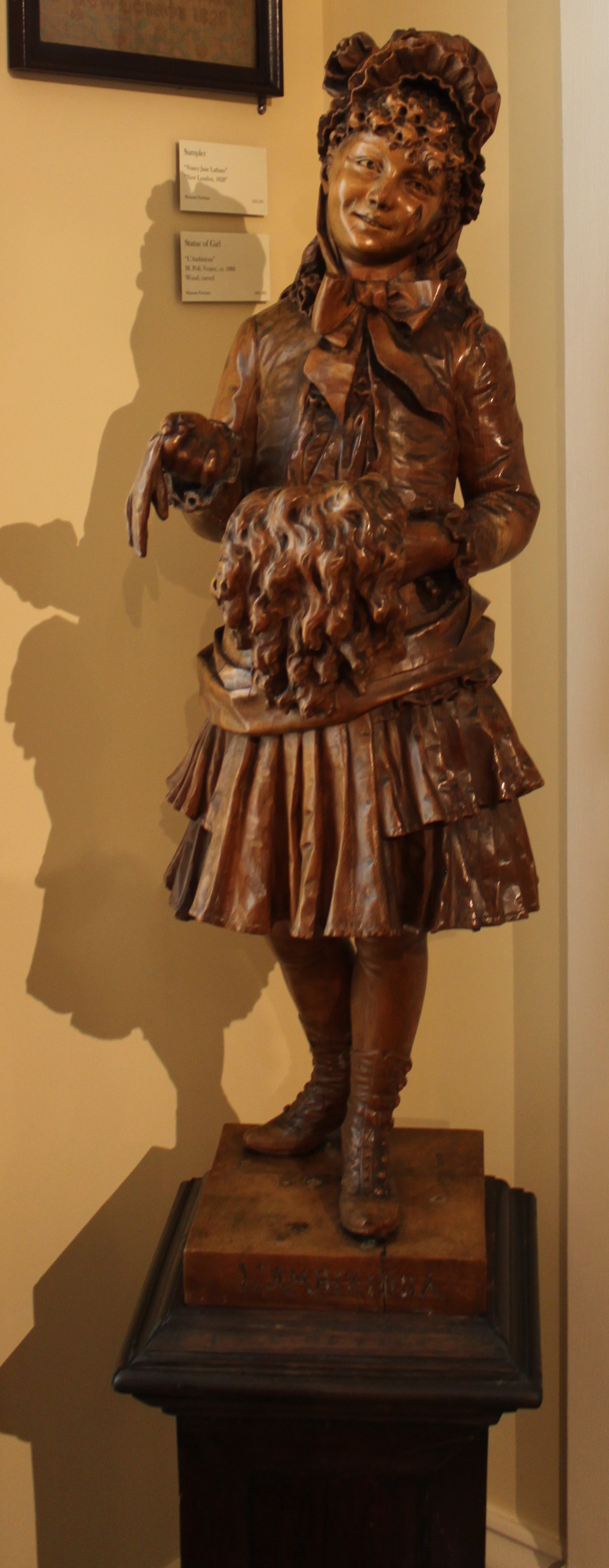 "Carved Wood Statue (Italian, 19th Century). The statue is of a young girl in a dress, bonnet and boots holding a fur muff and a glove. The statue is signed on the front of the wood platform base, ""L'Ambiziosa"" and it is signed on the side of the base, ""M. Poli, Venezia""."