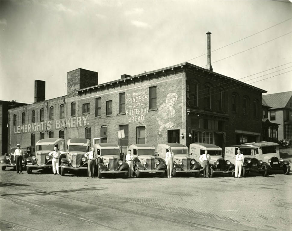 """Lembright's Bakery located at 179 East Market Street with several deliverymen and delivery trucks. The sign on the side of the building reads, """"Lembright's Bakery. The home of Princess and Butternut Bread."""""""
