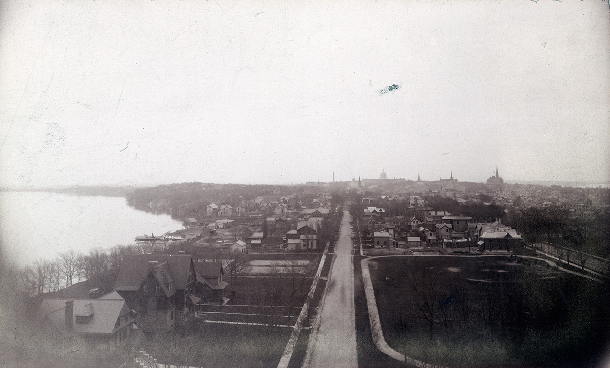 A cabinet card photograph of the skyline of Madison, Wisconsin from around 1890 taken from the western end of Langdon Street. The three houses in the lower left of the photograph sit on the lot that would later become Memorial Union. Also visible is the lot that would become the Red Gym.