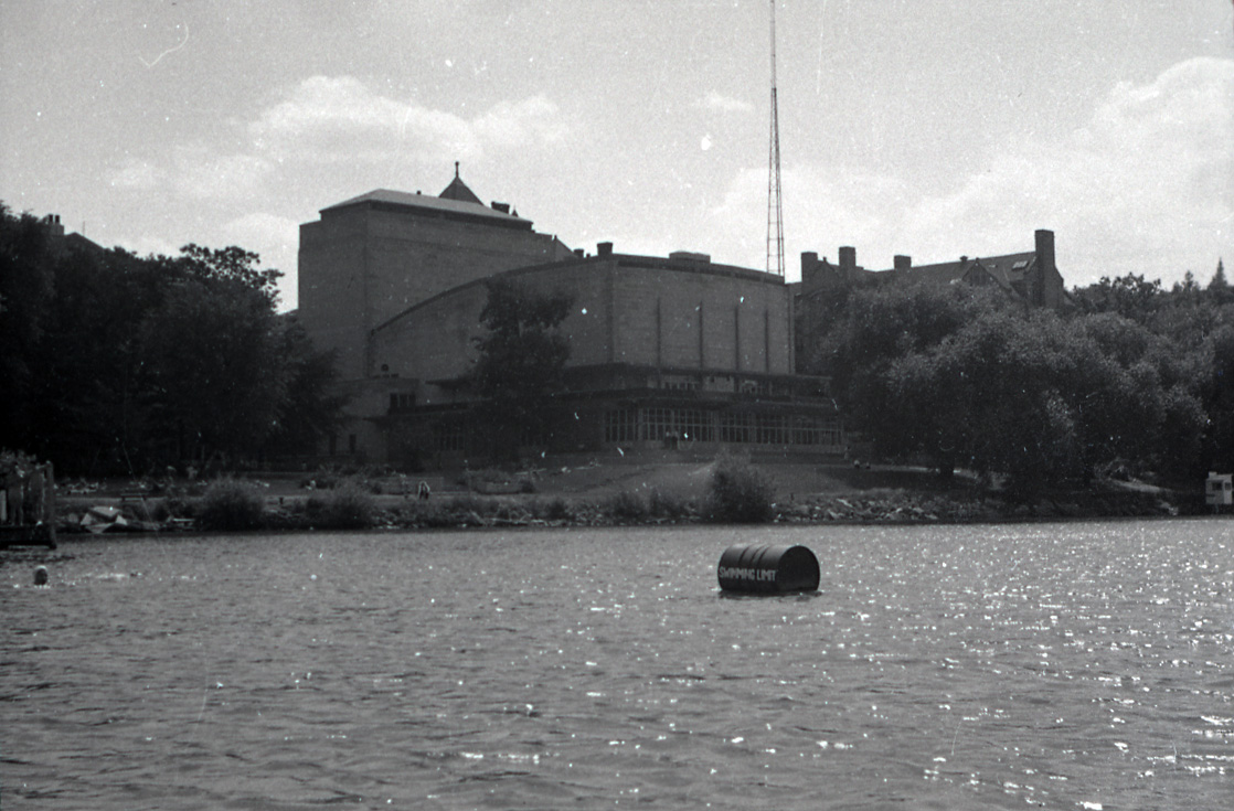 Photograph of Memorial Union taken from Lake Mendota. In the image, a barrell notes the edge of the swimming area, people are gathered on a the lawn, and Memorial Union sits above the lakeshore.