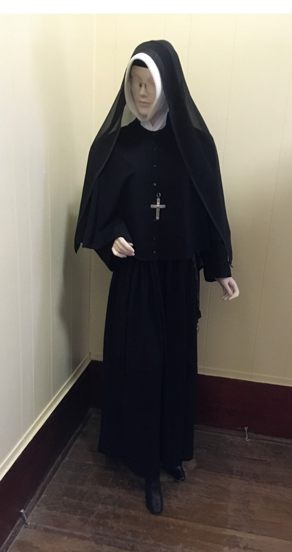 The mannequin is wearing the habit of the Religious of the Sacred Heart.  She is wearing a profession cross with the motto of the Society: CUAU- Cor Unum et Anima Unum.  One side has the Sacred Heart of Jesus and the other the Immaculate Heart of Mary.