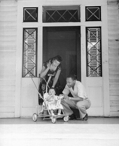 King and his wife and daughter, Coretta and Yolanda at the doorway of their home upon first moving in in 1954