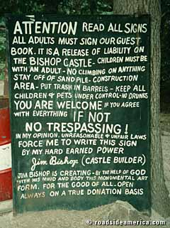 The sign regarding tourism of the castle, welcoming the tourists at their own risk. Signing the guestbook is agreeing to the rules, while failing to do so is considered trespassing.