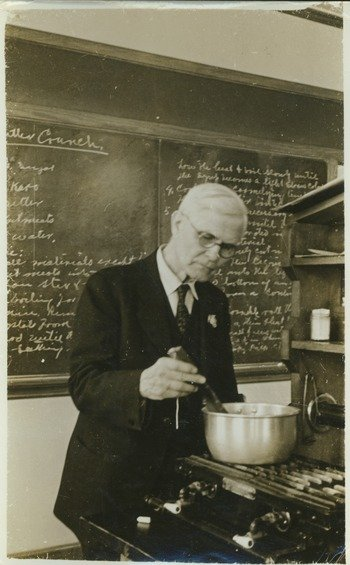 Walter W. Chenoweth stirring a pot on stove, in laboratory, ca. 1941.