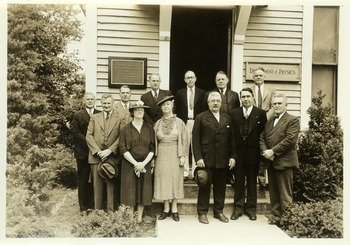 Hugh P. Baker (President, 1933-1947) standing with others in front of the Botanical Museum plaque, photo, ca. 1935.