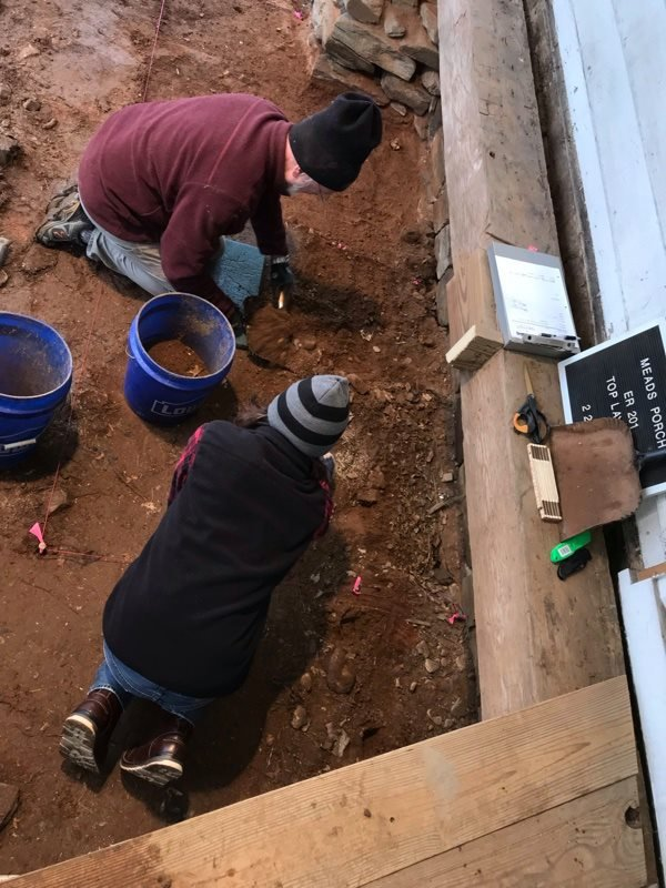 Liberty University archaeologist and student working on an excavation underneath the porch at Mead's Tavern.