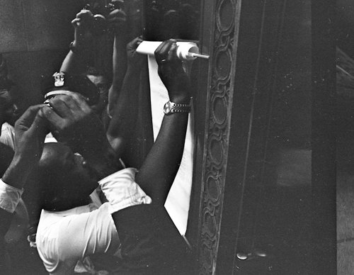 Echoing the 16th century protest of Martin Luther, King pins his demands to the door of City Hall.
