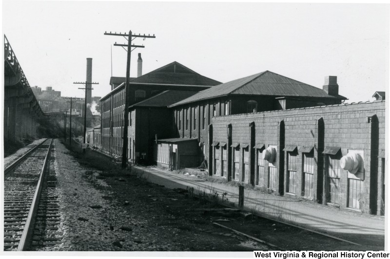 View of the east side of building along the railroad (now the Rail Trail) looking south. This image from the late 1980s depicts the original textile building as well as some additions. West Virginia and Regional History Center, WVU Libraries.