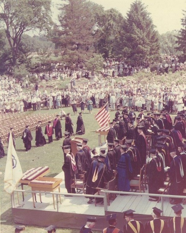Ceremony on Metawampe lawn, ca. 1950. Faculty members in academic gowns walk past the podium during ceremonies on the lawn in front of the statue of Metawampe, a gift from the Class of 1950.