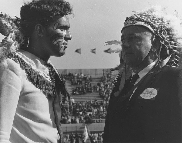 "Robert Bertram in Native American headdress, ca. 1980. Robert E. ""Bob"" Bertram of the Class of 1949 wears a Native American headdress while standing with an unidentified man, also in Indian dress, at McGuirk Stadium. Photo titled ""Metawampi""."