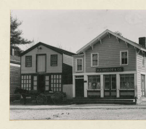 Briggs Store Owned by Hiram Briggs.  Company Name: H.H. Briggs Co. (Demolished in 1940 to make way for the post office) Horse and wagon are in front of the original Stoutenburg store. Charles Sylvester Piersaull Photograph Collection