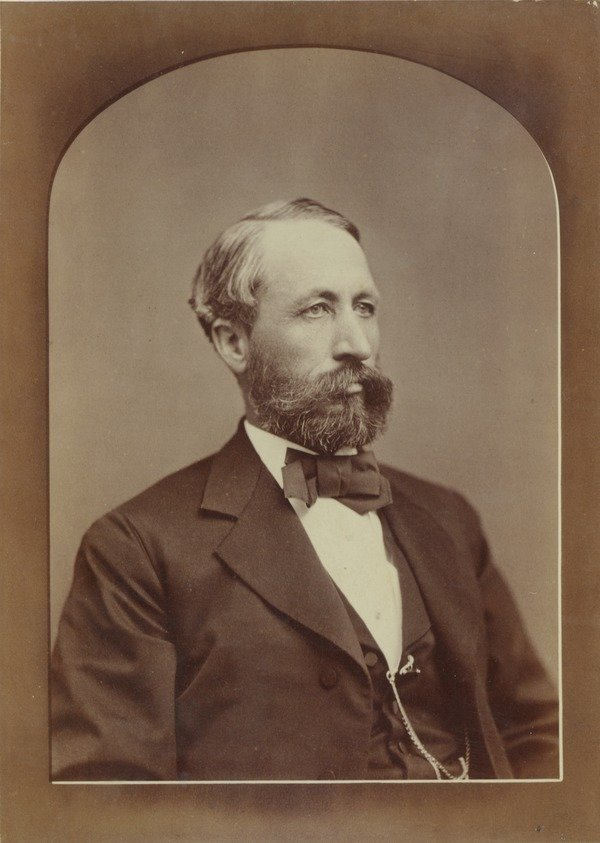 William S. Clark, ca. 1876. Formal portrait with bow tie and watch fob. Photo mounted on white cabinet card with name of photo studio at the bottom.