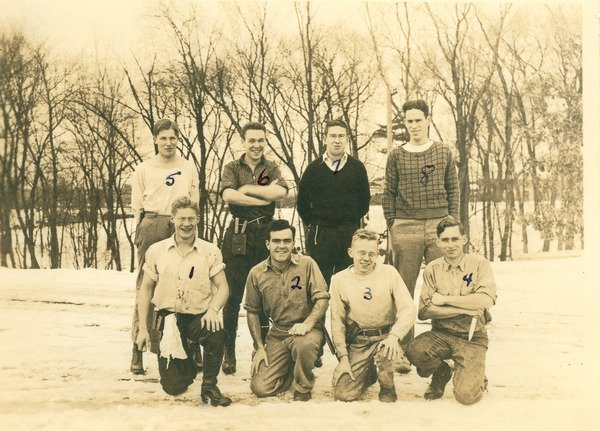 Fraternity men posing outdoors in the winter, ca. 1938. Class of 1939 members from various fraternities pose near the campus pond in the winter, including #6, (top row, 2nd from left), Phi Sigma Kappa member Emerson Wallace Grant.