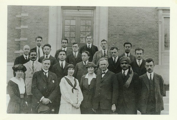 """Kenyon L. Butterfield, 1922. Kenyon Butterfield is shown in the front row of a group of people who are posing on steps in front of a building. Written on the back of the photo: """"College Cosmopolitan Club. 10 nationalities represented. About 1922"""". To"""