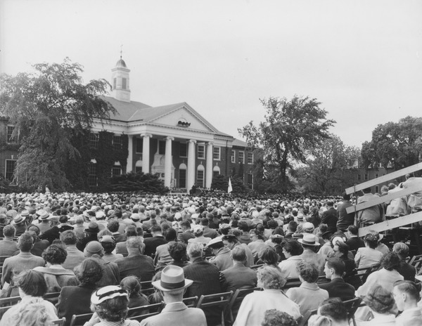Commencement at Goodell Library, ca. 1955. A crowd of spectators, some in seated in bleachers, listen to a speaker as Commencement ceremonies are held in front of Goodell Library (possibly in 1955).