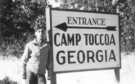 A soldier from the 506th Infantry Regiment standing at the entrance to Camp Toccoa while posing for a picture.