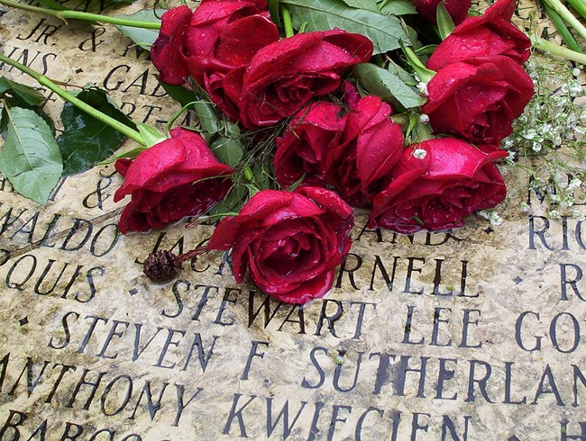 Roses placed above the names engraved in stone at the AIDS Memorial in Golden Gate Park