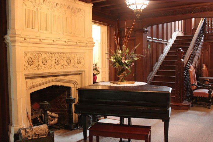 The mansion's large foyer with stone carved fireplace, piano and open staircase.