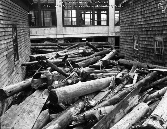 Lumber washed into town during the flood. Much of the damage was caused by the movement of industrial debris down from the many lumber mills operating along the Union River. (Courtesy of Maine Historical Society).