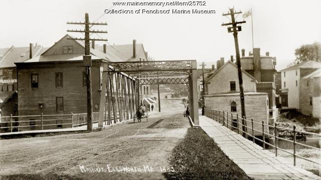 Main St. Bridge a few years before being swept away by floodwaters. Note how close to the riverbank these various structures were before the disaster. (Maine Historical Society).