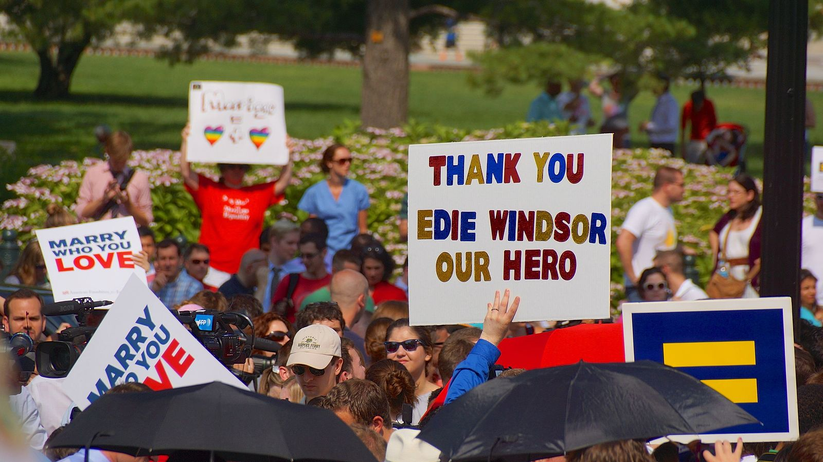 A participant during a Pride march holding a sign thanking Edith Windsor, a hero