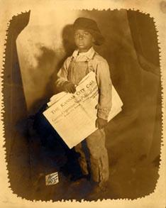 Photograph of a unidentified newsboy holding the Kansas City Call.