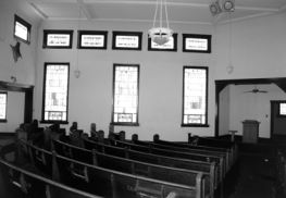 Inside the church: note the plaster walls, stained glass windows, and simple light fixture. This photo was included in the property's 2004 registration form for the National Register of Historic Places.