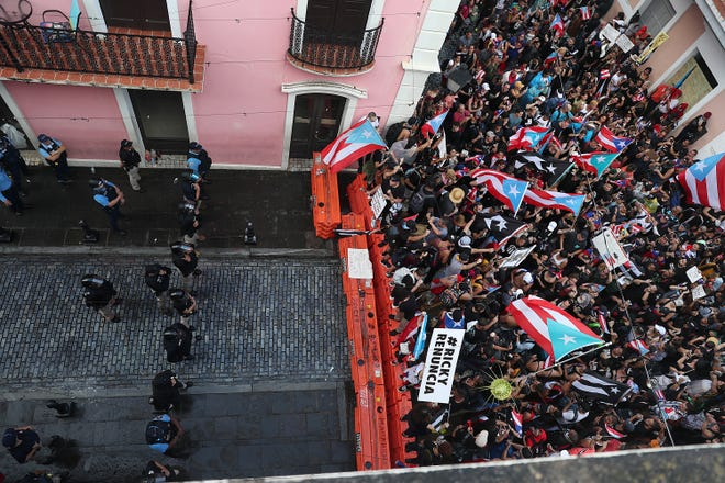 "Protesters taking over ""La Calle Fortaleza"" and being stopped by a police barricade outside the governor's official residence"