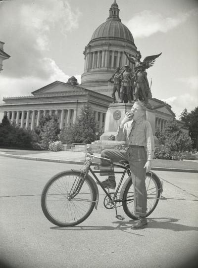 Shows the Legislative building, Winged Victory, and Governor Langlie's son Jimmie with a bicycle in the foreground, ca. 1940.