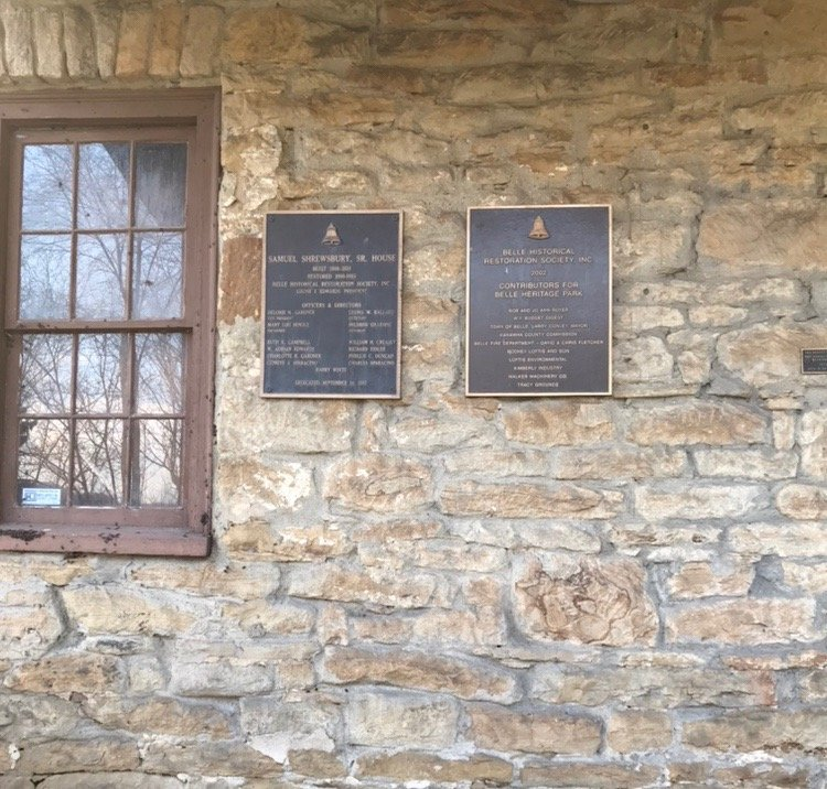 The brass plaques on front porch inscribed with the names and dates of the house dedication ceremony.