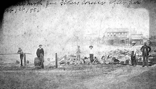 Firefighters and civilians stand after the fire.