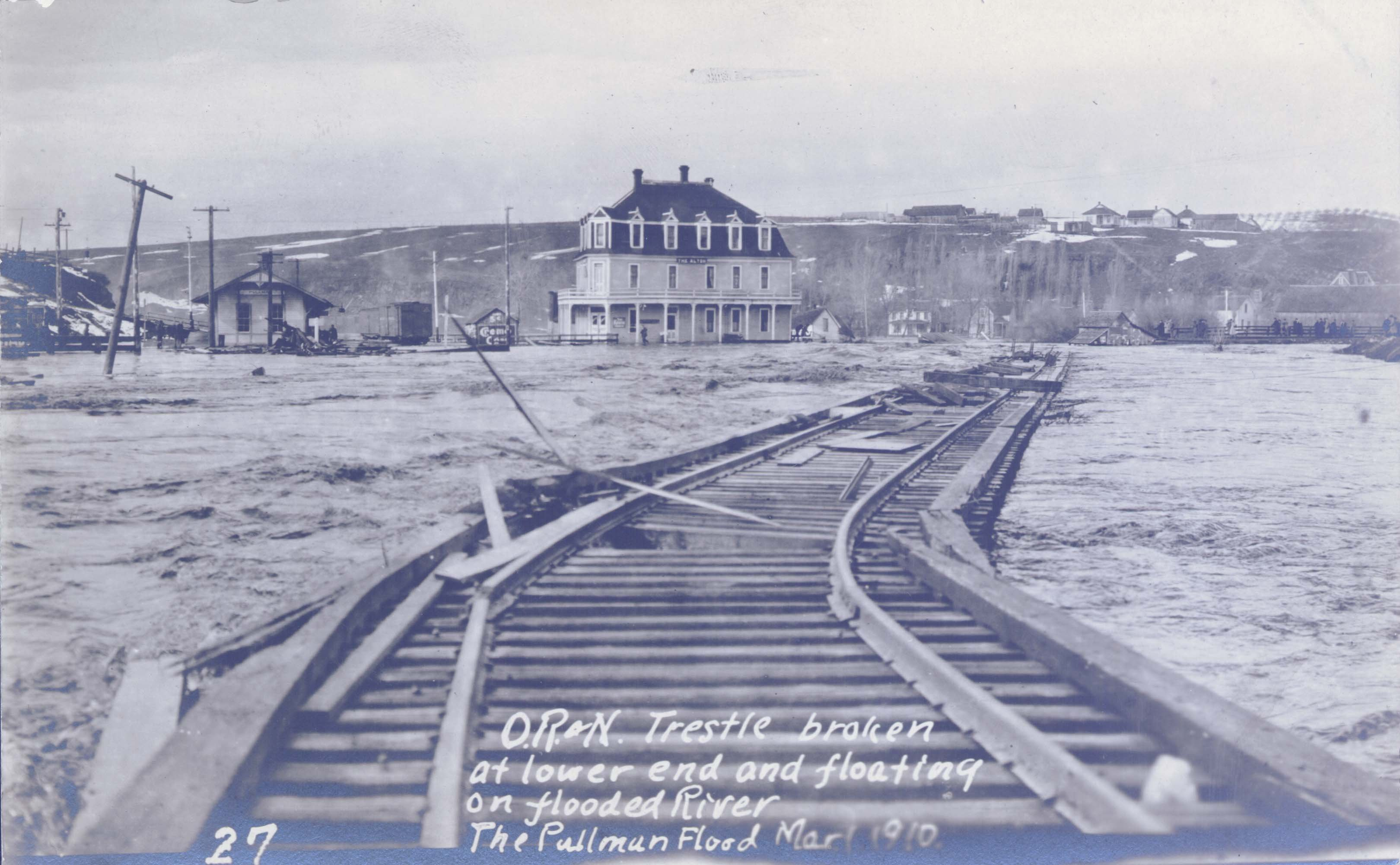 Looking west at the former Union Pacific Depot, with the Oregon Railroad & Navigation Trestle broken at the lower end and floating in flooded Palouse River in 1910. Taken by Robert Burns. Courtesy WSU Special Collections. http://content.libraries.wsu.edu/