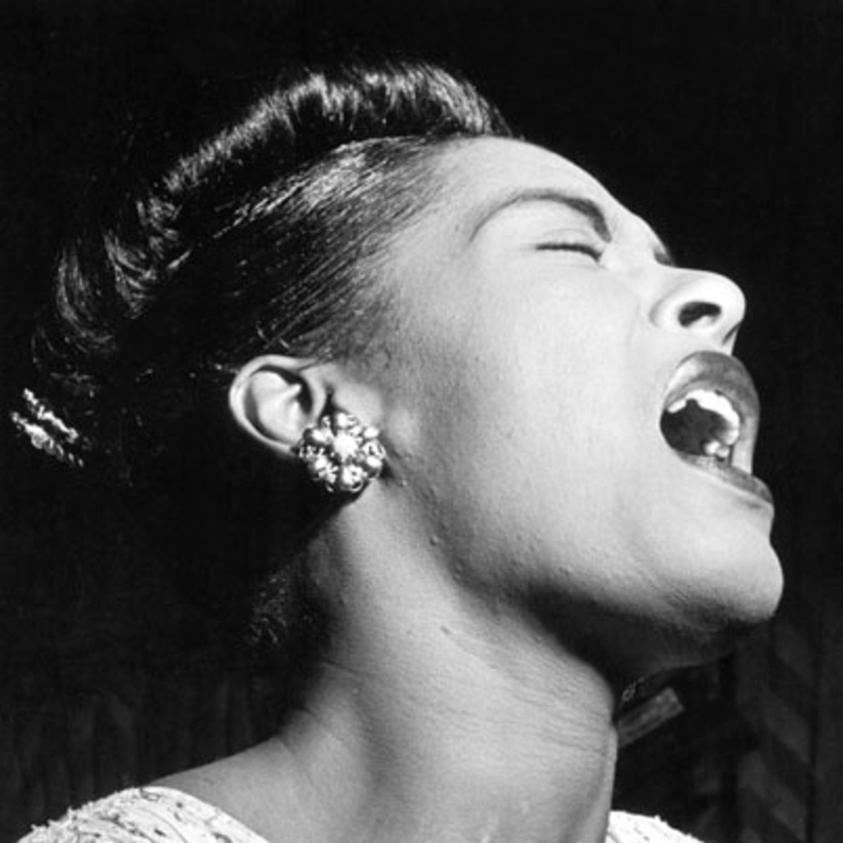 A photo of Billie Holiday performing. She was renowned for her ability to manipulate a microphone in order to be able to purr into it quietly or sing at very high volumes. Her style of working the microphone became the standard as others such as Frank Sin