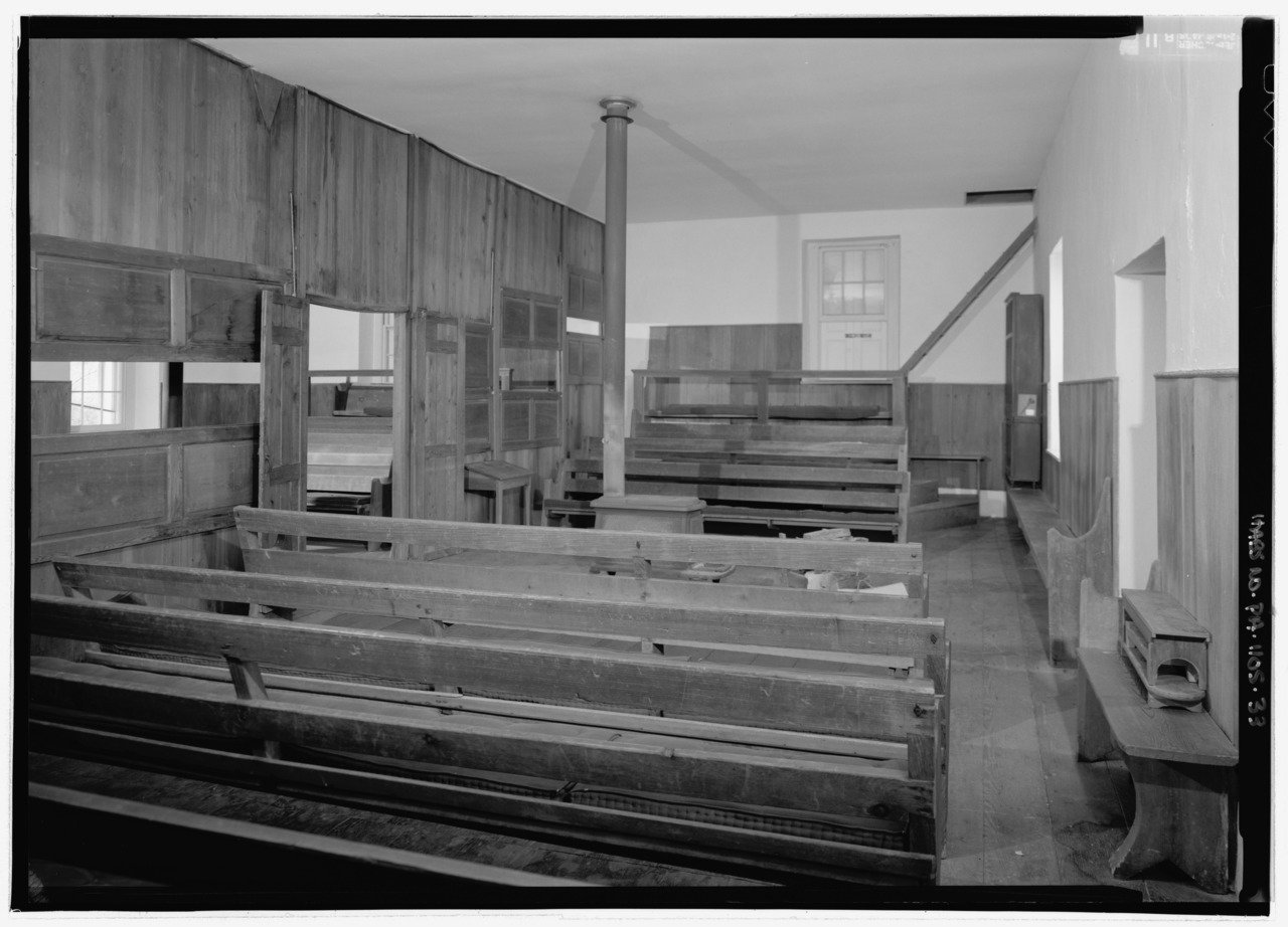The simple interior of the meetinghouse is usual among the Society of Friends.