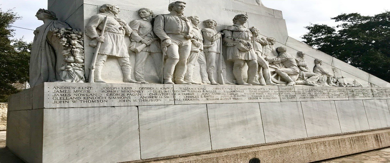 Side angle of Travis, Crockett, the eight soldiers, and the inscribed names of the fallen heroes.