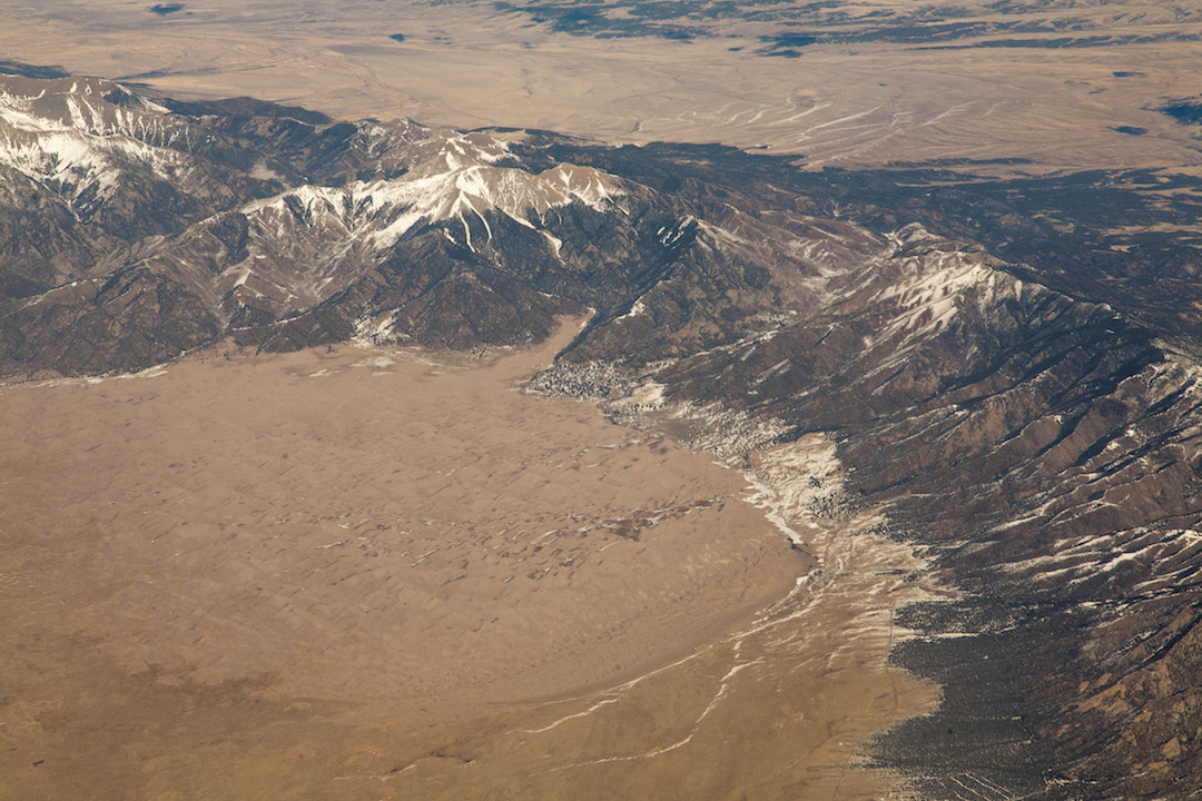 Aerial view of the dunes and the Sangre de Cristo Range. The visitor center is not visible but is located on the bottom right of the photo.