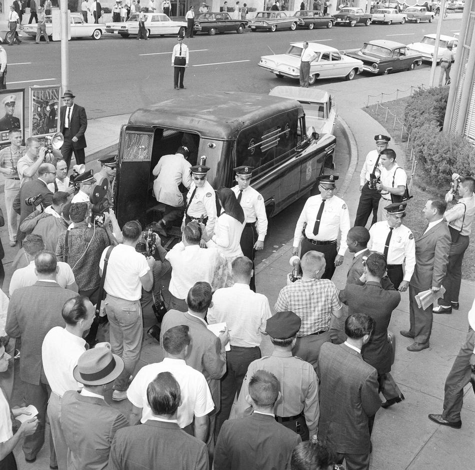 "Fifteen Freedom Riders that arrived on a second bus in Jackson, Miss., are loaded into a paddy wagon at the bus station, May 24, 1961. They entered the ""whites only"" waiting room and were arrested for being in violation of state laws."