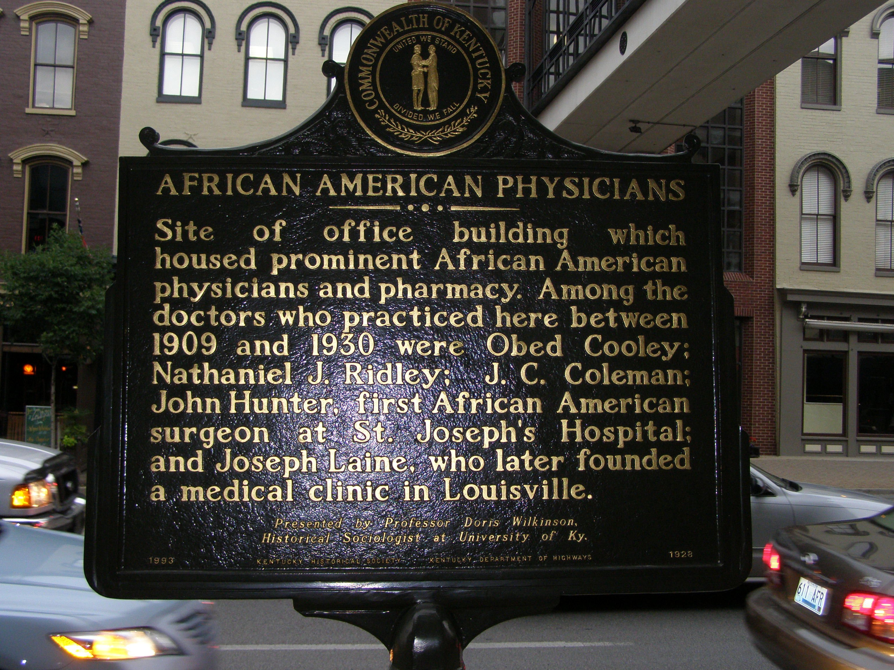 This is the front of the African American Physicians marker. It states that it is the site of the building that housed prominent African-American physicians and pharmacy. This marker provides information about specific doctors.
