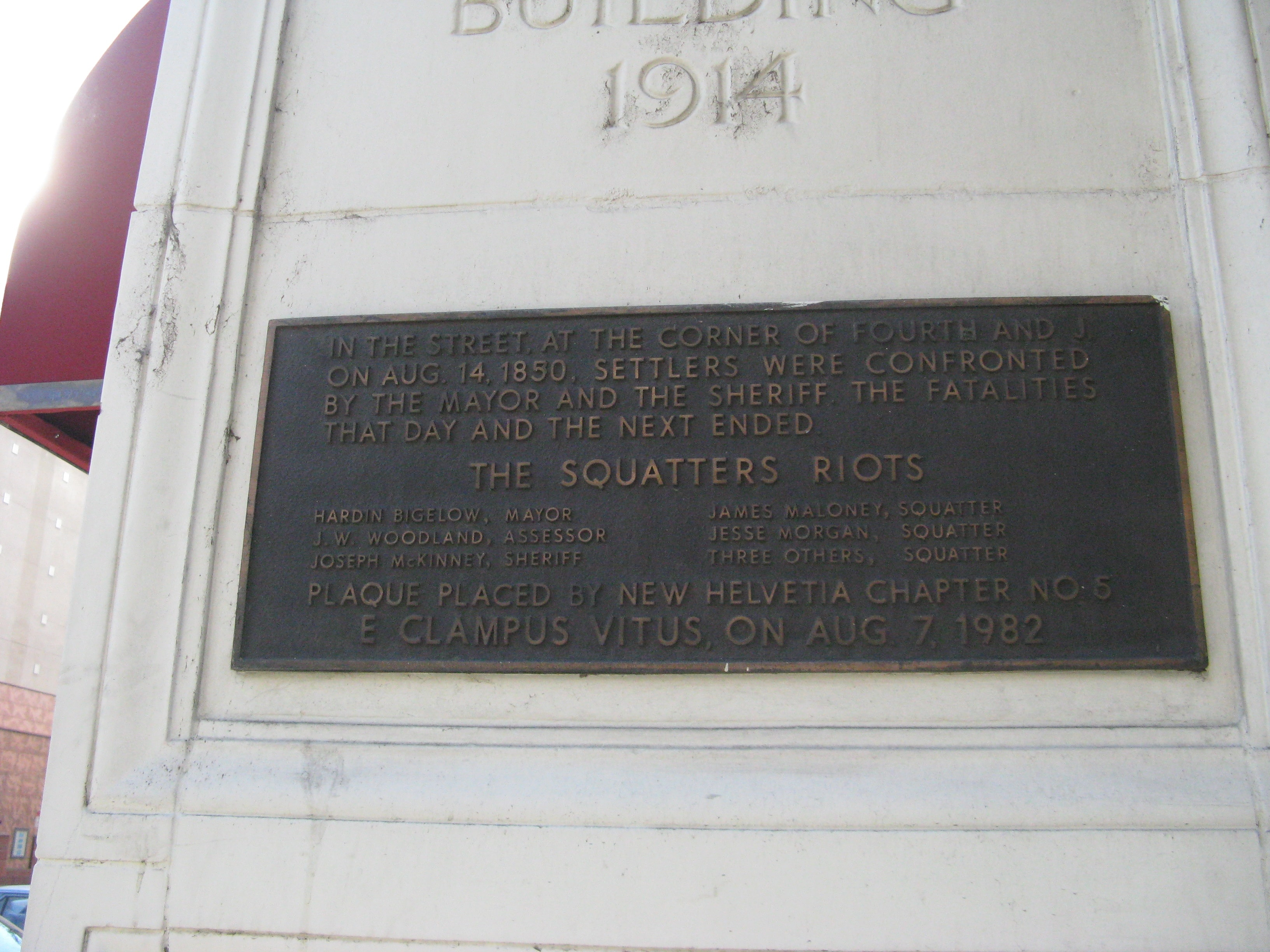 The 1982 commemorative plaque placed on the NE corner of the California Fruit Building, near where the line of squatters made their stand. The listed dead did not all perish in this gunfight (photo by Syd Whittle, hmdb.org).