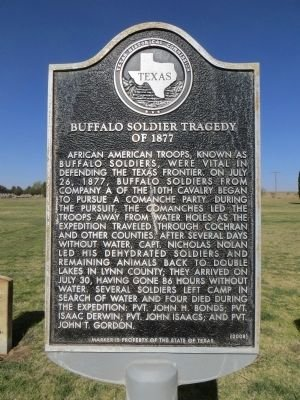 Photo of marker by state highway 214, directly behind it lies the four headstones