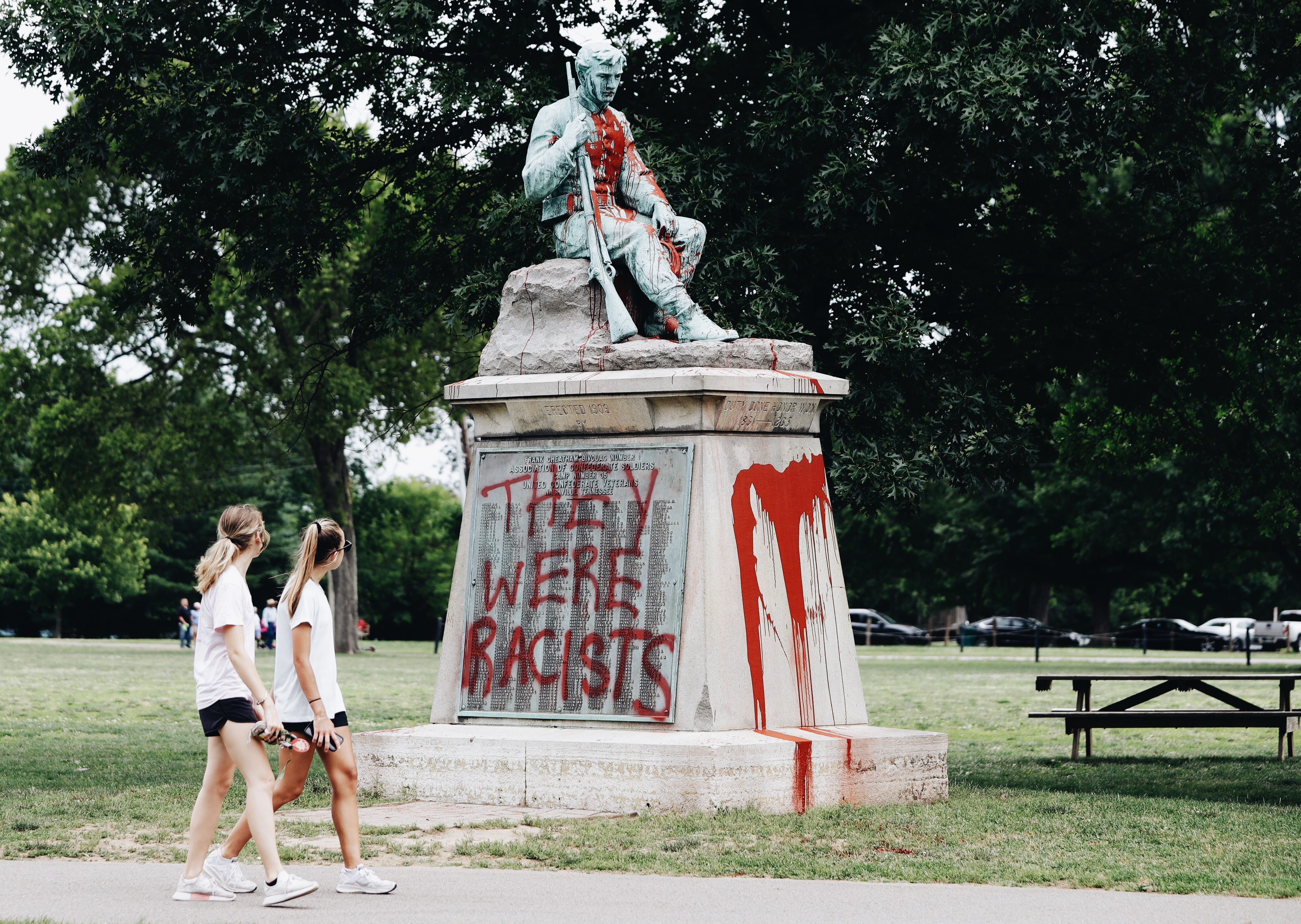 On June 17th, 2019, the vandalized statue remained painted in red while observers passed by.