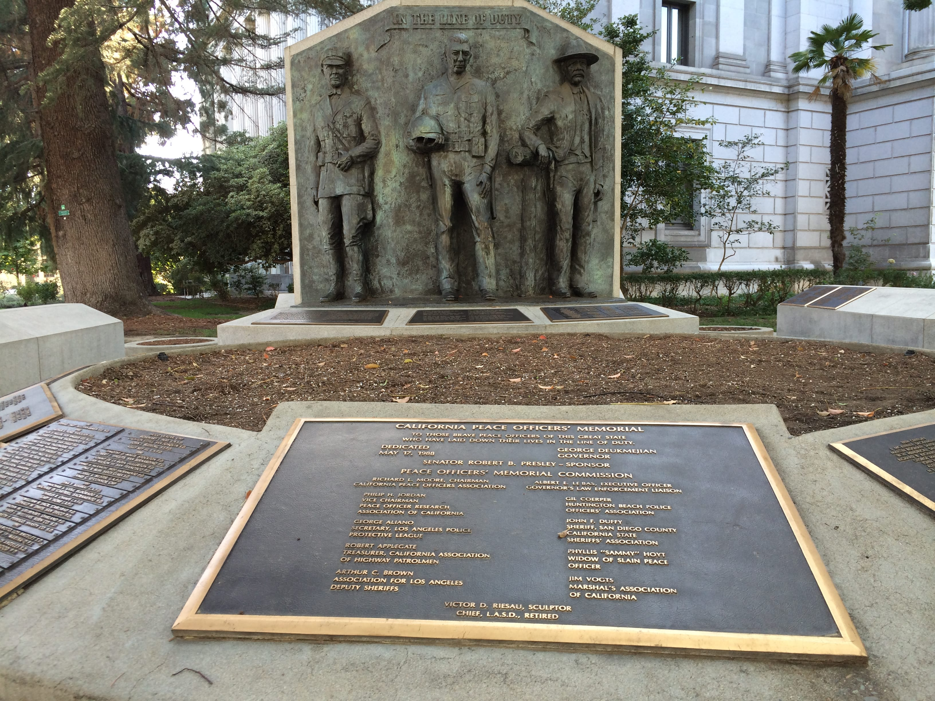 A closer view of one of the memorial plaques with the three 9-foot statues in background.