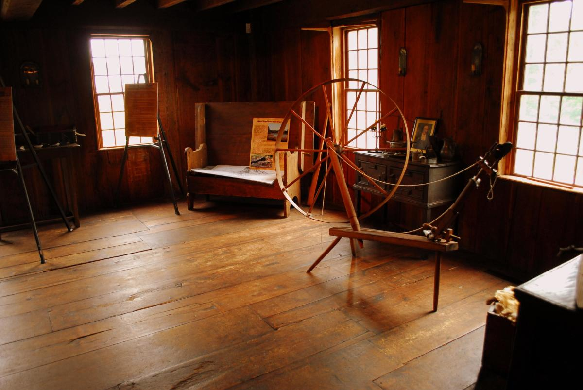 A spinning wheel sits in one of the rooms within Smith's Castle.
