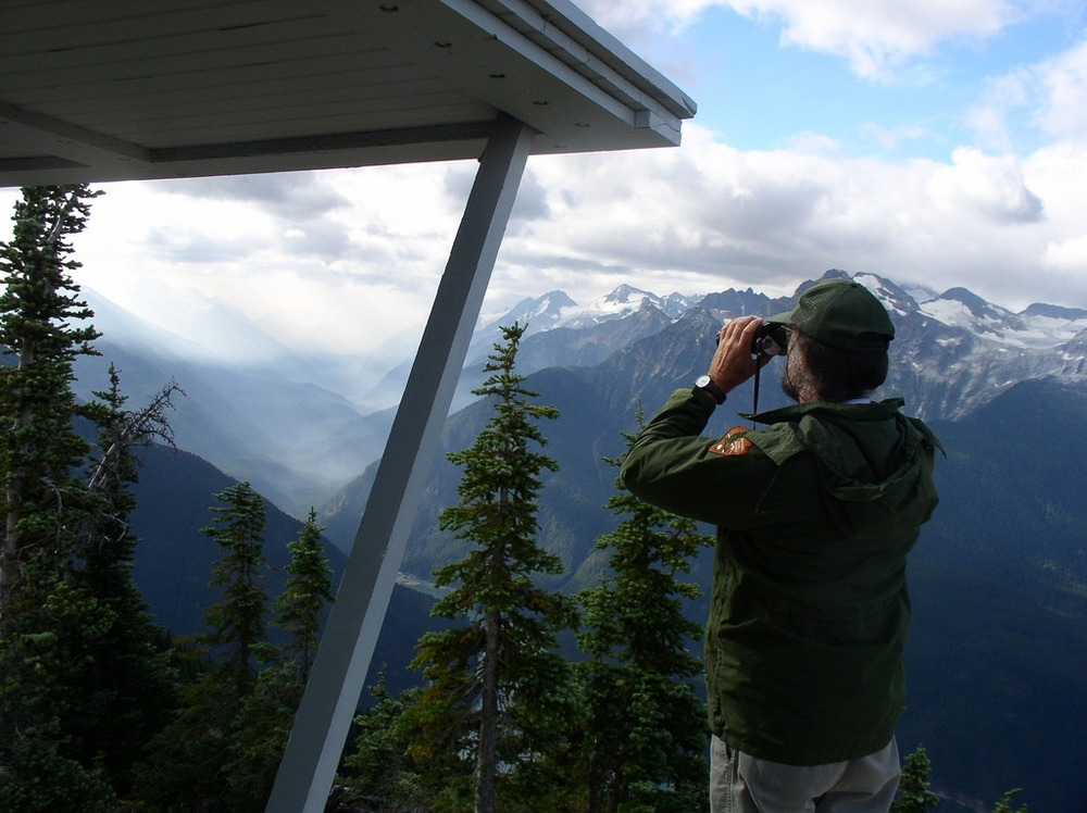 A park ranger looks through his binoculars from Sourdough Lookout.