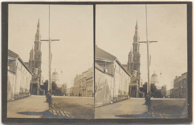 The unpaved streets of late 19th Century Sacramento can be seen in this stereograph from 11th and K Streets, from which the spire of the Cathedral can be seen in the background (CA State Library).