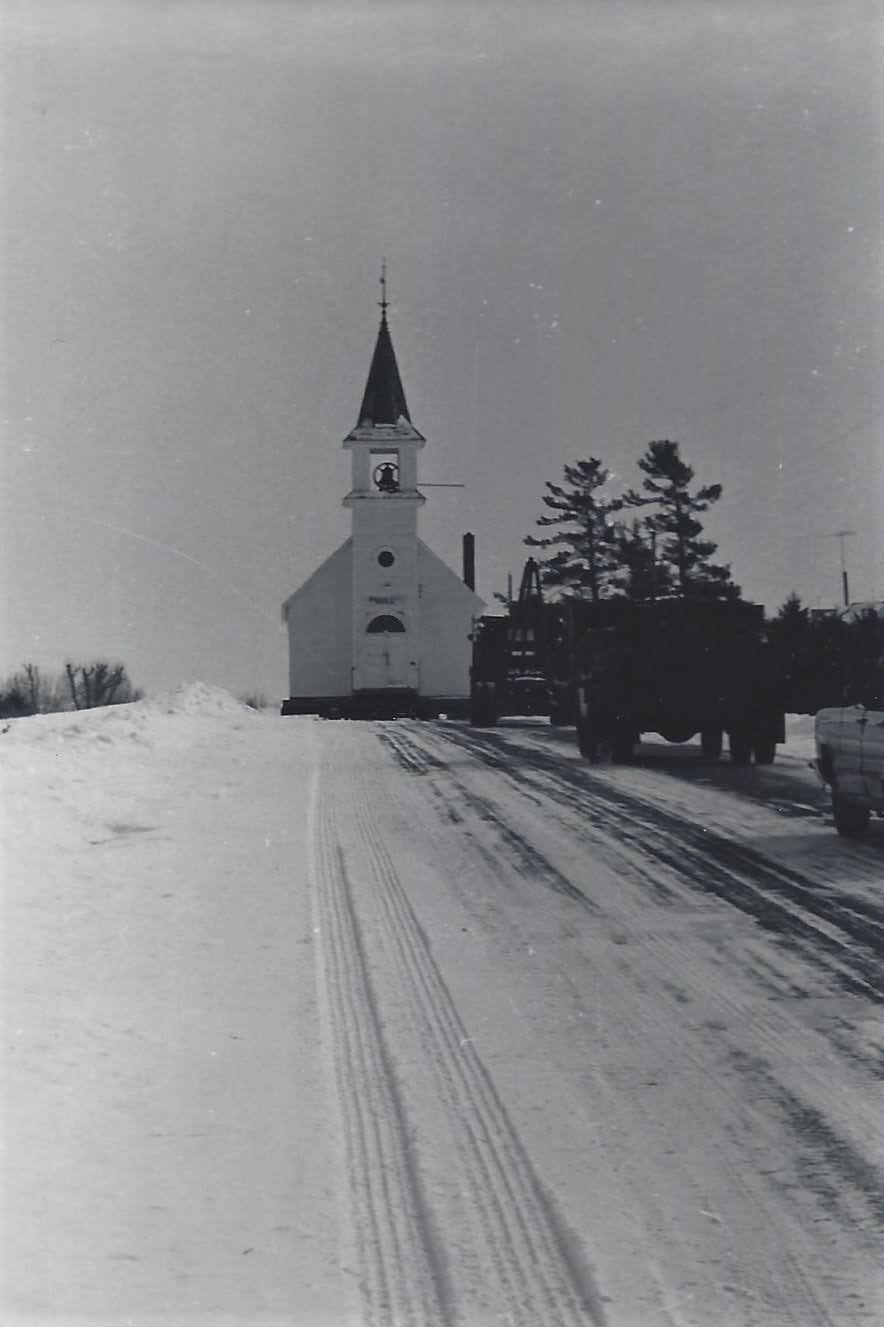 Caravan of vehicles leading the machinery carrying the church along a snowy road.
