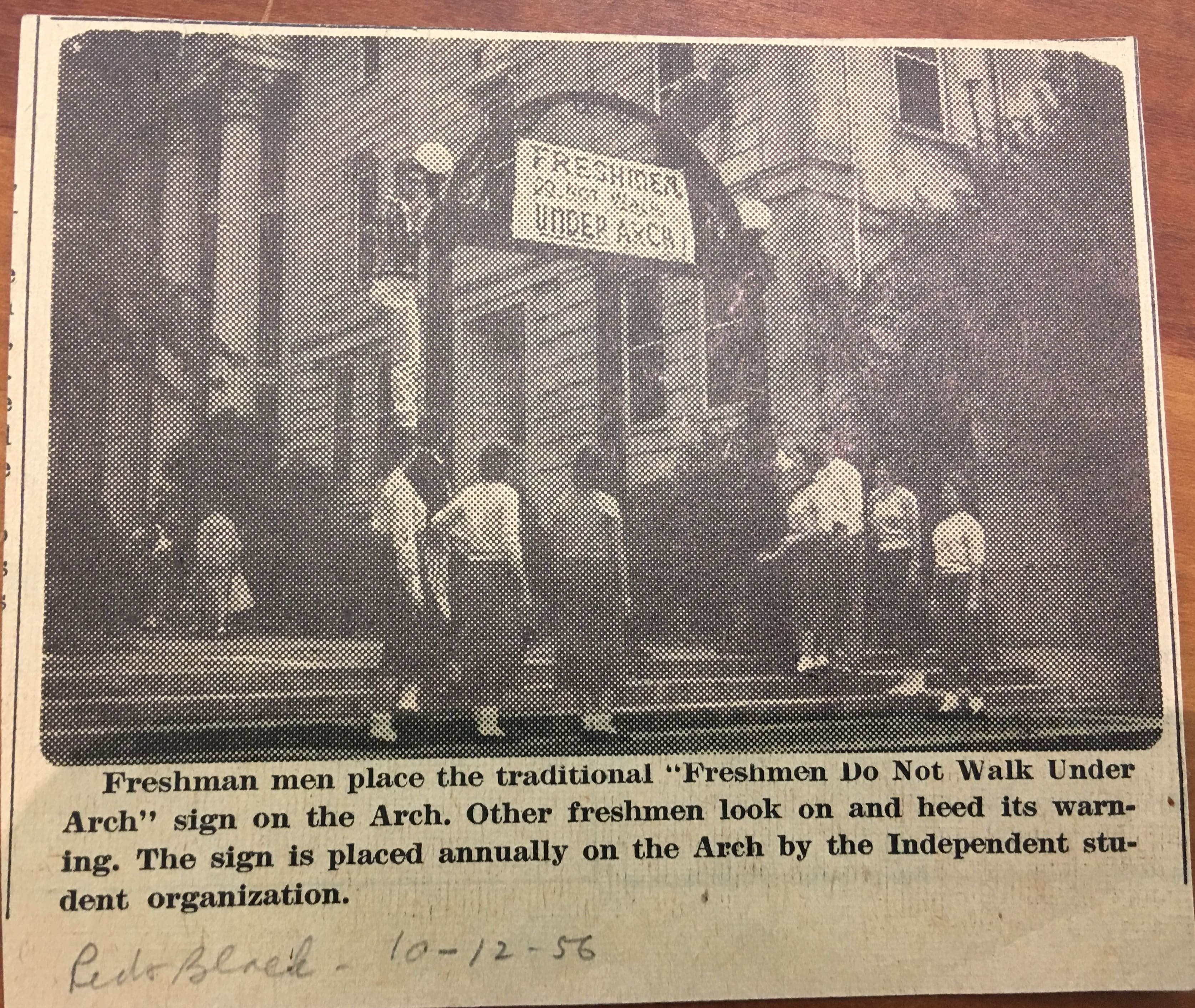 A historic photo from 1956 showing students placing a sign on the Arch warning freshmen to avoid walking under it