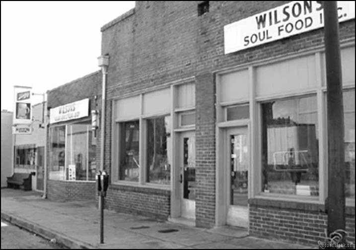 Black-owned businesses have thrived at Hot Corner since the 1950s. Featured above is M.C. Wilson's styling shop and restaurant, circa 1981.