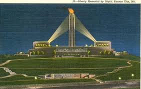 The Liberty Memorial Tower lit up at night with flame at top