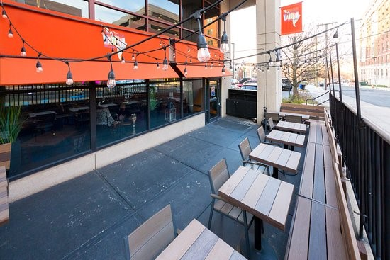 The outside of Esquina Latina, showcasing the outdoor seating provided to customers and the street accessibility.